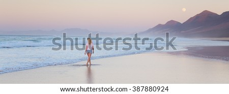 Woman walking on sandy beach in sunset. Waves sweeping away her traces in sand. Beach, travel, concept. Copy space. Panoramic composition.