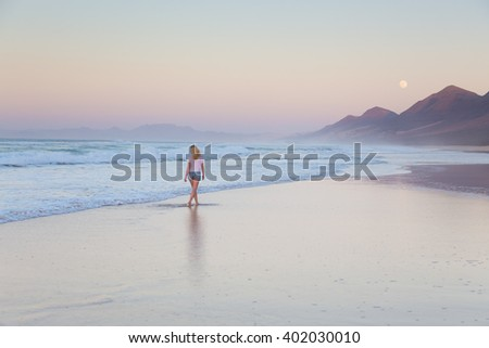 Woman walking on sandy beach in sunset. Waves sweeping away her traces in sand. Beach, travel, concept. Copy space.