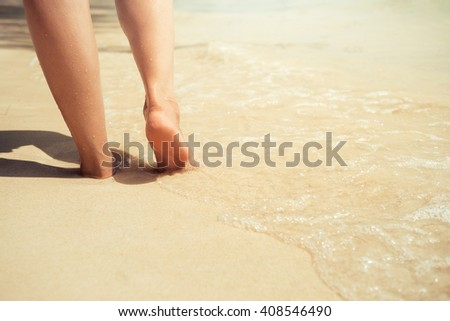 Woman walking on the beach - stock photo