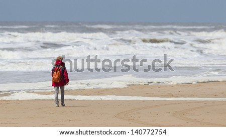 Woman walking on the beach during a storm - stock photo