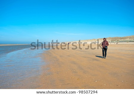 Woman walking on the beach in spring