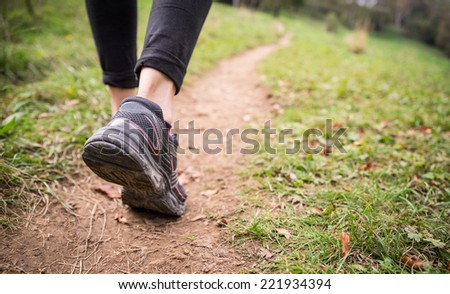 Woman walking on the path - Sportive girl running in a forest along a track - stock photo