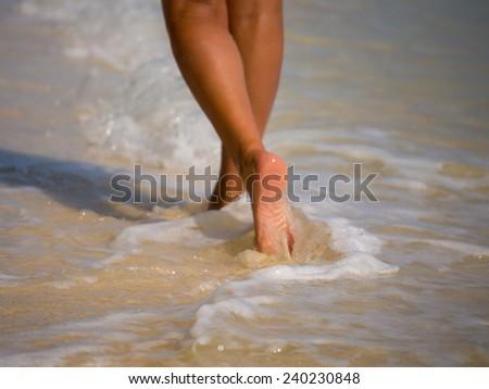 Woman walking on the sandy beach - Selective focus - stock photo