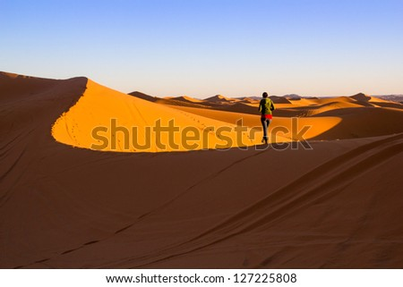 Woman walking on top of a sand dune