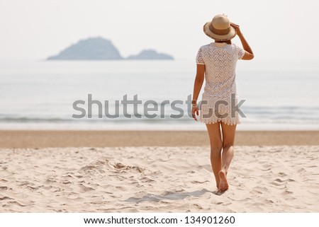 Woman walking on tropical beach - stock photo