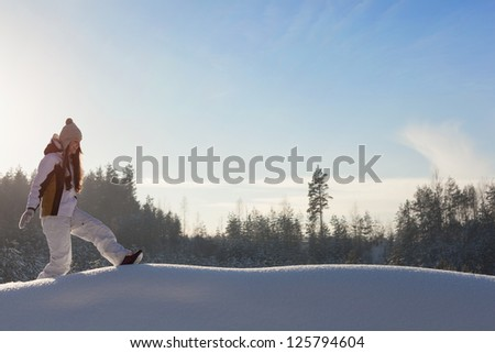 woman walking through snowy woodland, outdoors