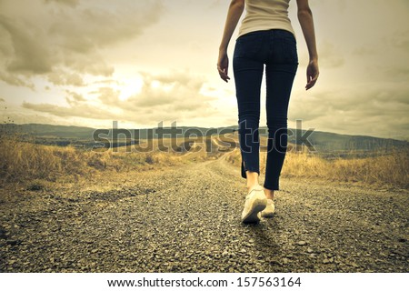 woman walking towards unknown places - stock photo