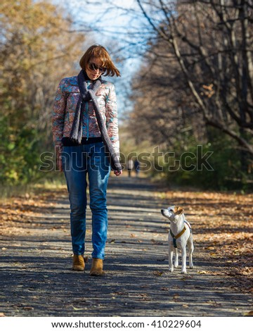 woman walking with a dog in autumn park, the age of 40