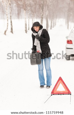 Woman walking with gas can car snow breakdown trouble winter - stock photo