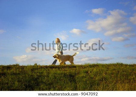 woman walking with her dog golden retriever in nature