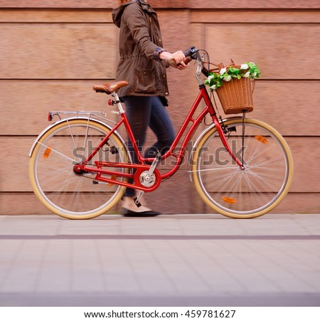 Woman walking with red bike