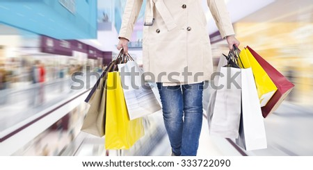 woman walking with shopping bags in mall. - stock photo