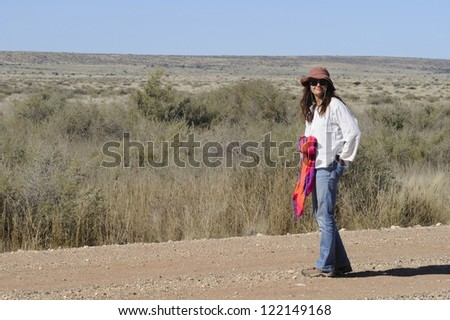 Woman walks along a remote road in the Karroo, Putsonderwater, Northern Cape, South Africa