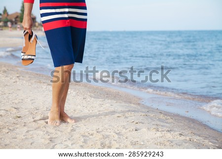 Woman walks along a sandy beach with sandals in her hands