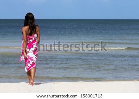 Woman walks an empty beach. Woman in a dress walks on the beach towards the sea. Female bottom goes on sea beach. Back of woman on the beach.Walking along the sandy beach with a horizon of blue sea.