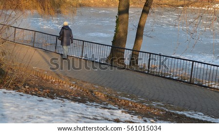 woman walks around a small icy lake in a park on a winter day