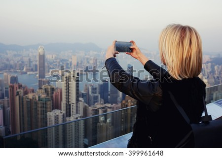 Woman wanderer is taking photo on mobile phone camera of big New York city, while is standing on a roof high building.Hipster girl is shooting video of the view on cell telephone during trip in China - stock photo