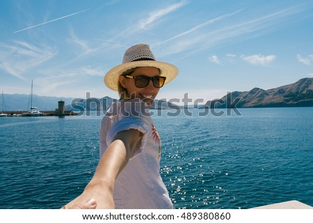 Woman wanting her man to follow her in vacation or honeymoon to beach by the sea