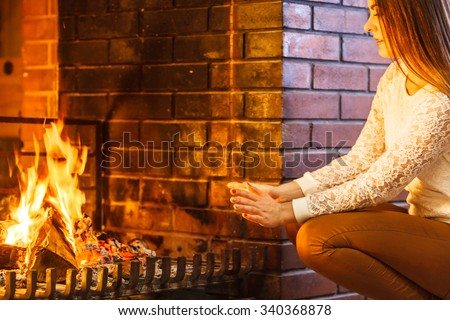 Woman warming hands up at fireplace. Young girl relaxing resting. Winter at home. - stock photo