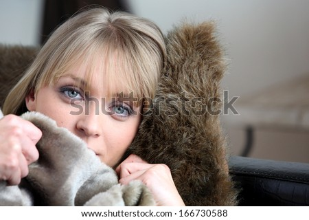 Woman warming herself up under blanket - stock photo