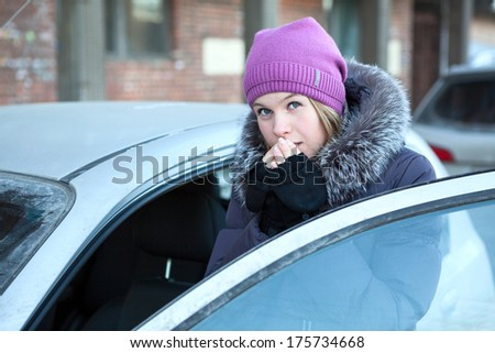 Woman warming his hands near the car - stock photo