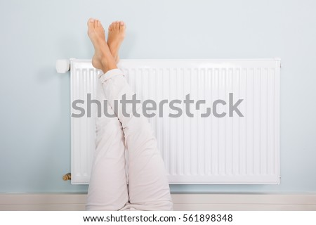 Woman Warming Up Her Feet On White Radiator At Home