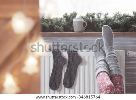 Woman warming up with feet on heater Winter woolen socks drying on a heater, christmas lights, decorations and hot drink  - stock photo