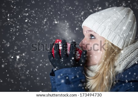 Woman warming up with hot drink - stock photo