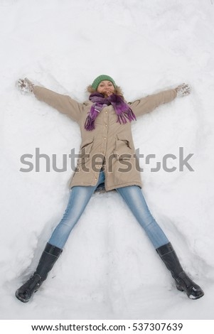 Woman Warmly Clothed In A Cold Winter Forest Makes Snow Angel Figure At Park