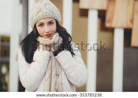 Woman warmly clothed in a cold winter on the beach with the sky in the city street. Portrait of young pretty funny smiling girl in cold weather. young happy woman having fun outdoor.  - stock photo