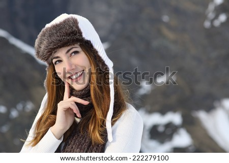 Woman warmly clothed thinking in winter and looking at side - stock photo
