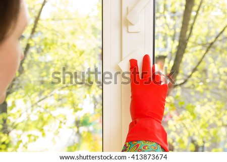 woman washes a window in the house. melamine sponge eraser. housewives. view from the window. window cleaning. beautiful gloves. cleaning service - stock photo