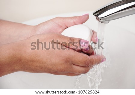 Woman washes her hands under the tap with soap