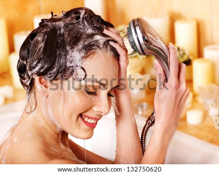 Woman washes her head at home bathroom. - stock photo