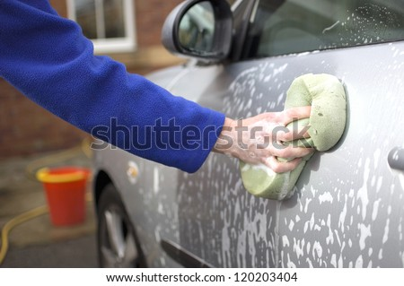 Woman washing car outside her home - stock photo