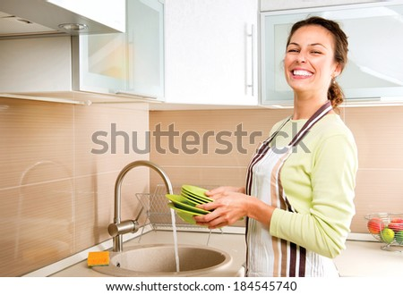 Woman Washing Dishes. Kitchen. Dishwashing. Woman doing housework at home - stock photo