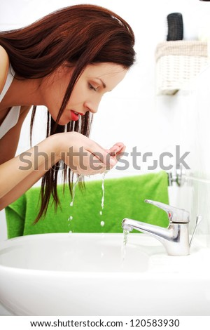 Woman washing face with water above bathroom sink - stock photo