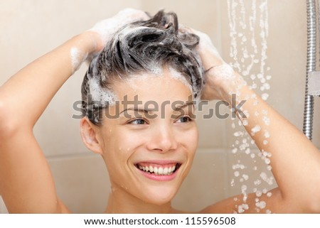 Woman washing hair with shampoo foam in shower smiling happy looking at running warm water. Beautiful mixed race Asian Chinese / Caucasian female model in bathroom.