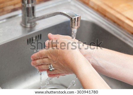 woman washing hand in kitchen sink