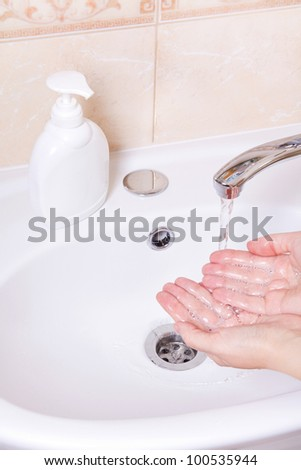 Woman washing hands in bathroom close up