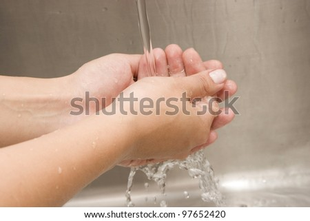Woman Washing hands Under Running Water White Sink Chrome spout - stock photo