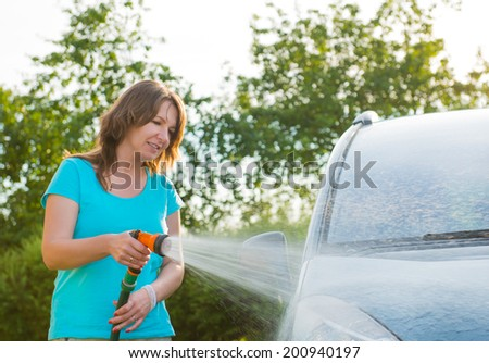 Woman washing her car in garden without detergents in ecological way.