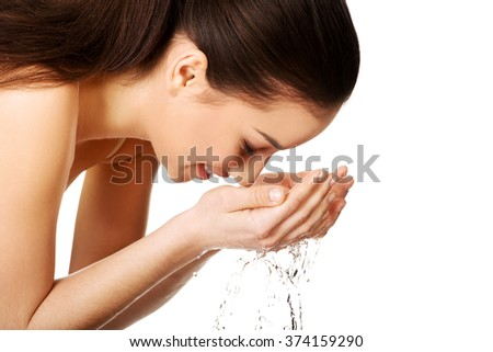 Woman washing her clean face.