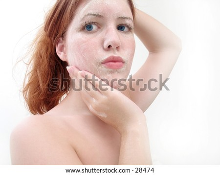 Woman washing her face with soap, looking away from camera.