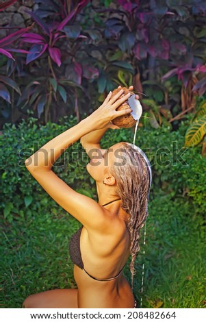 Woman washing her hair with the pure coconut milk - stock photo