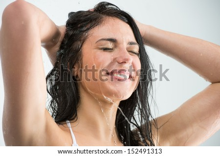 Woman washing her head while showering with happy smile and water splashing. Beautiful Caucasian female model home in shower cabin.