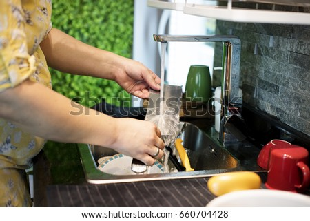 Woman washing kitchen utensils at the sink