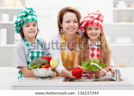 Woman washing the vegetables with the kids in the kitchen at the sink