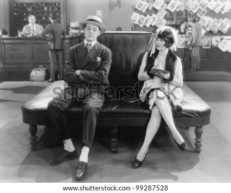 Woman watching a sleeping man on a leather couch