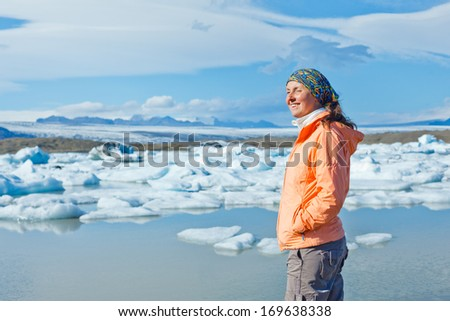 Woman watching icebergs at Jokulsarlon glacial lagoon near Vatnajokull National Park, southeast Iceland - stock photo